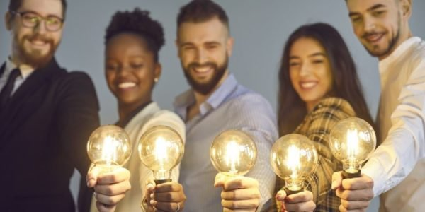 Diverse group of young businesspeople smiling and holding shining light bulbs to represent sharing a useful idea.