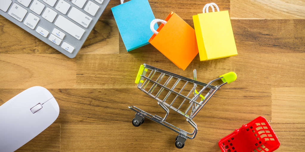 Overturned shopping cart near keyboard representing shopping cart abandonment on e-commerce.
