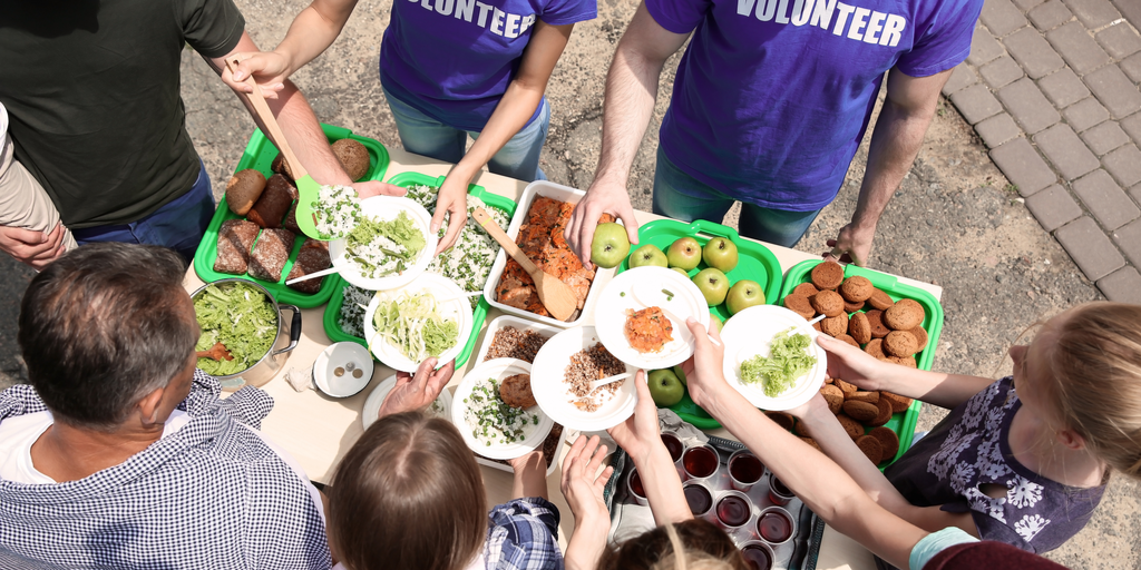 Volunteers serving food to people in need, picture as an example of visual storytelling.