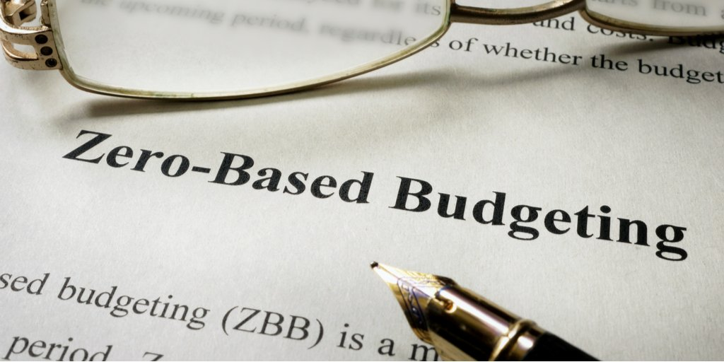 Paper with zero-based budgeting written on it, with glasses and pen resting on it.