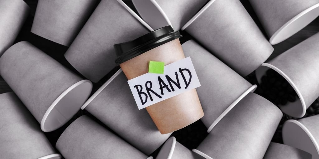Brown coffee cup with Brand text standing out among gray cups.