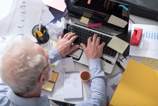 Top view of man working at a cluttered desk.