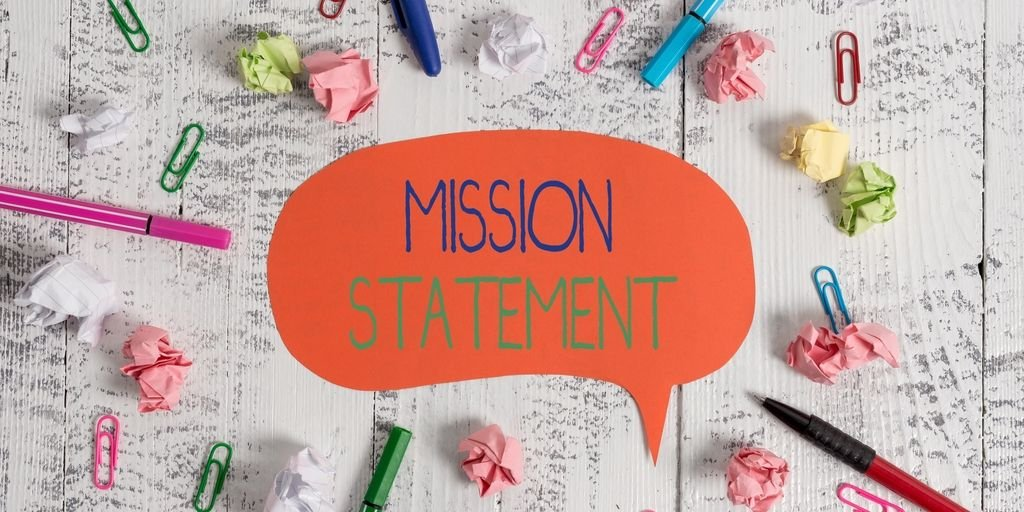 Mission statement cutout surrounded by paper clips and pens.