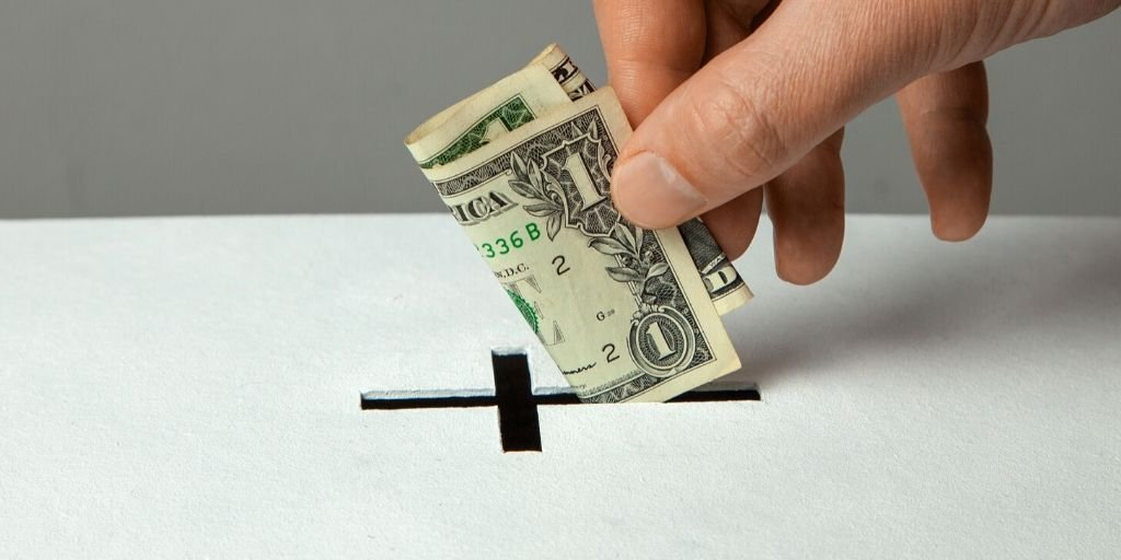 Hand putting dollar in box through slot shaped like cross as a form of church giving.