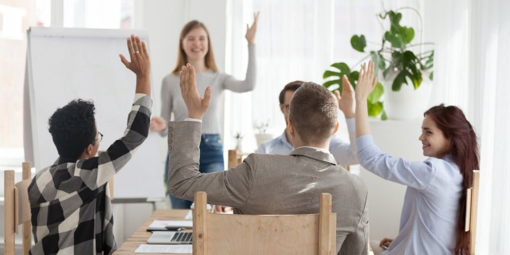 Employee standing in front of team, all with raised hands, representing leadership as the key to how to motivate staff.