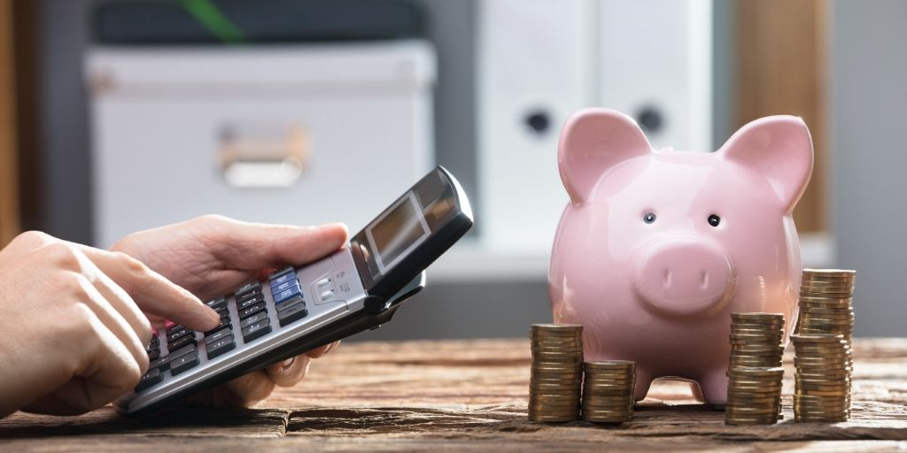 Man using calculator next to piggy bank and coins, demonstrating marketing on a budget.