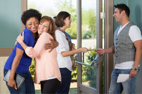 Friends hugging at church, showing the importance of inviting people to church.