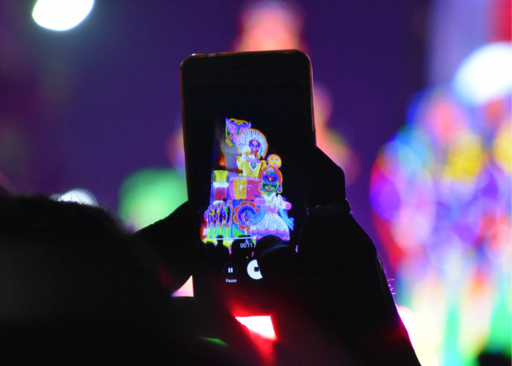 hands holding up mobile device recording colorful event for Instagram Stories