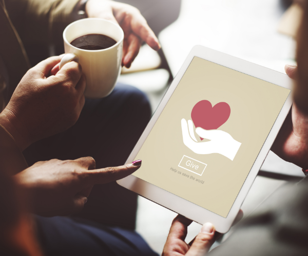 """three people looking at tablet, one holding a cup of coffee. tablet shows hands holding a heart with word """"give"""""""
