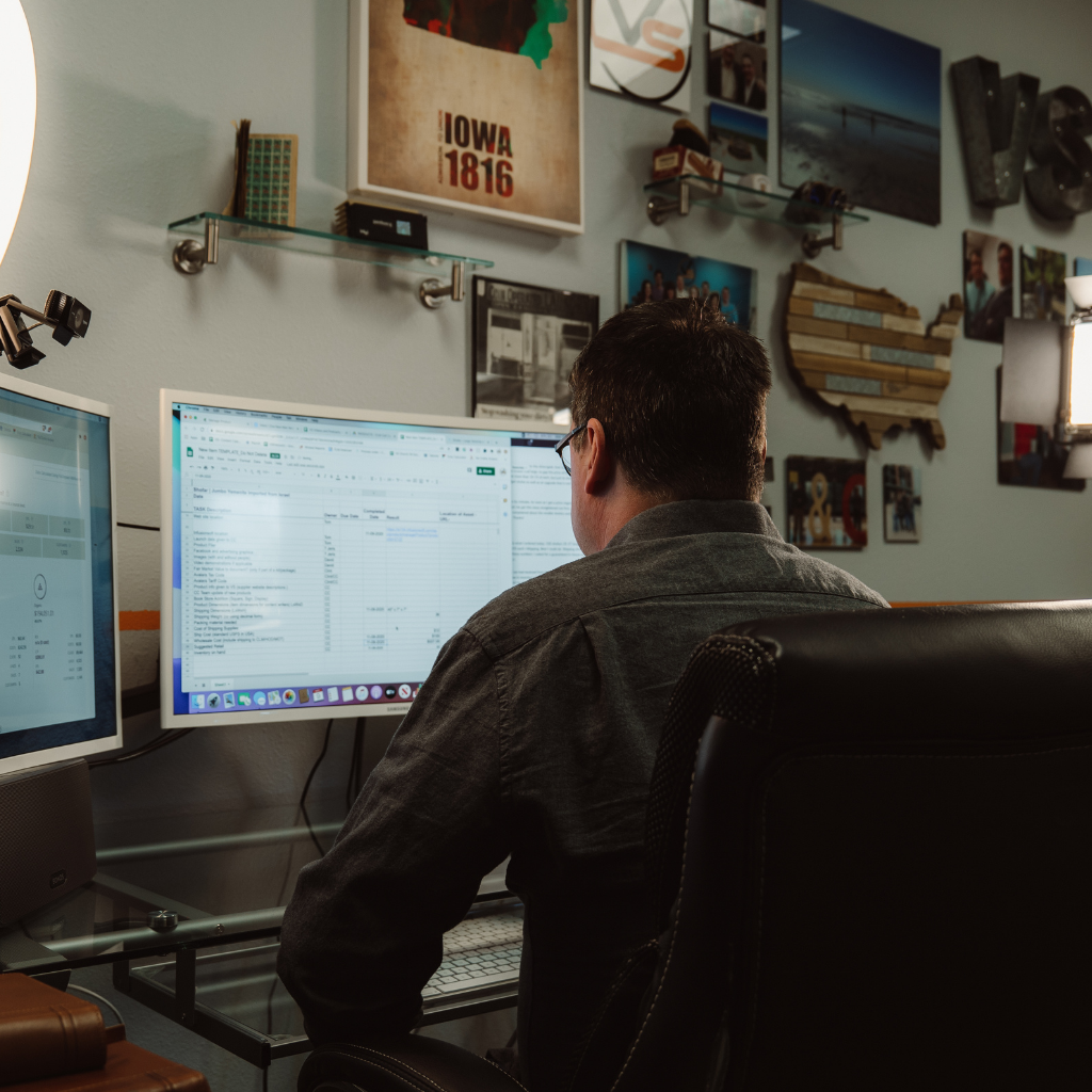 man doing IT work at desk with dual screens
