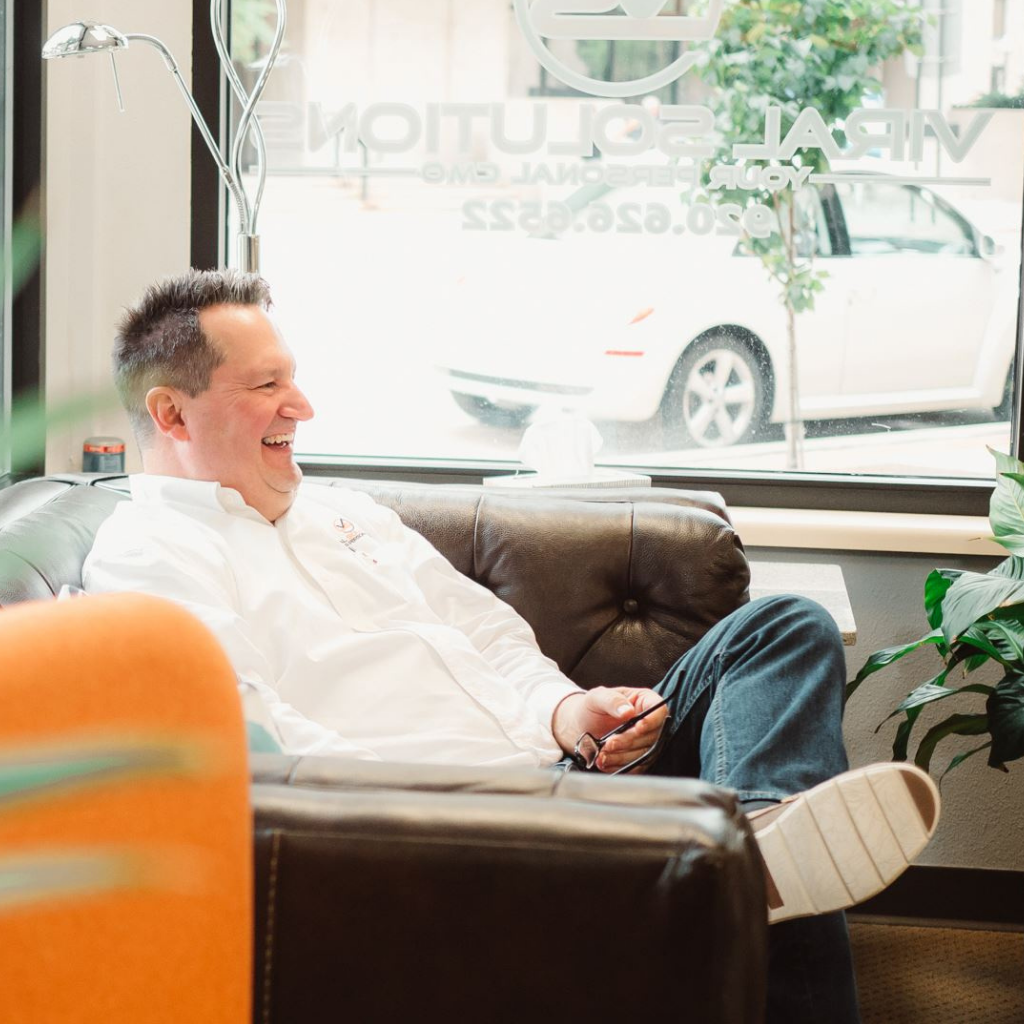 man sitting on couch with joyful expression