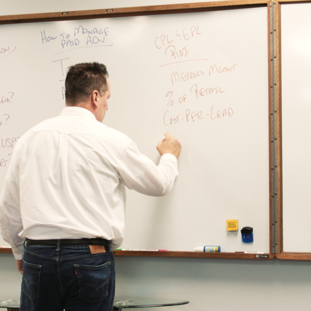 man writing explanations of SEO Services on whiteboard
