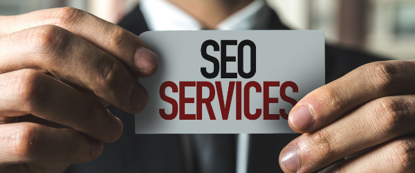 Man holding SEO Services Sign