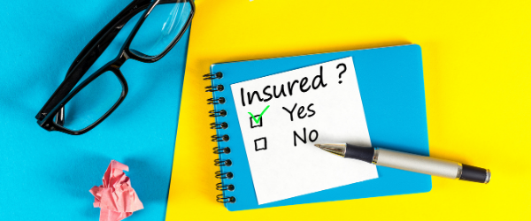 Notepad asking if you are insured. Glasses and crumpled paper next to notepad