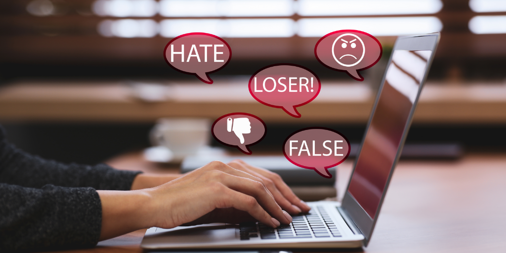 Hands typing on laptop with speech bubbles showing words like hate, loser, and false as well as thumbs down and frowny face.