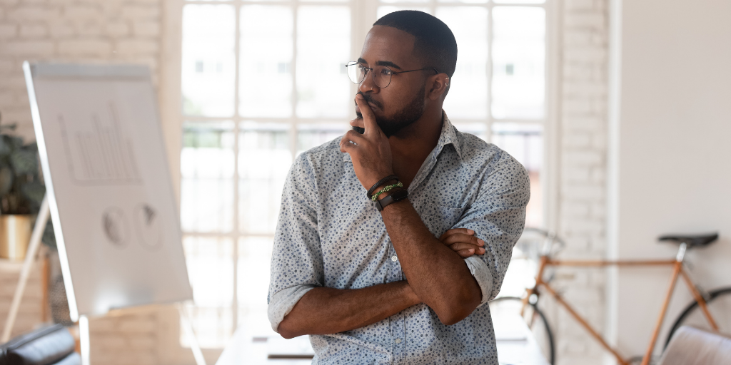 Black male business owner in industrial office space looking pensive.