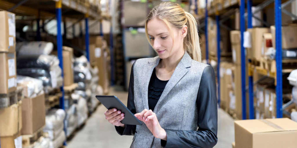 Businesswoman in her warehouse looking at product thinking ideas for her business using a tablet device.