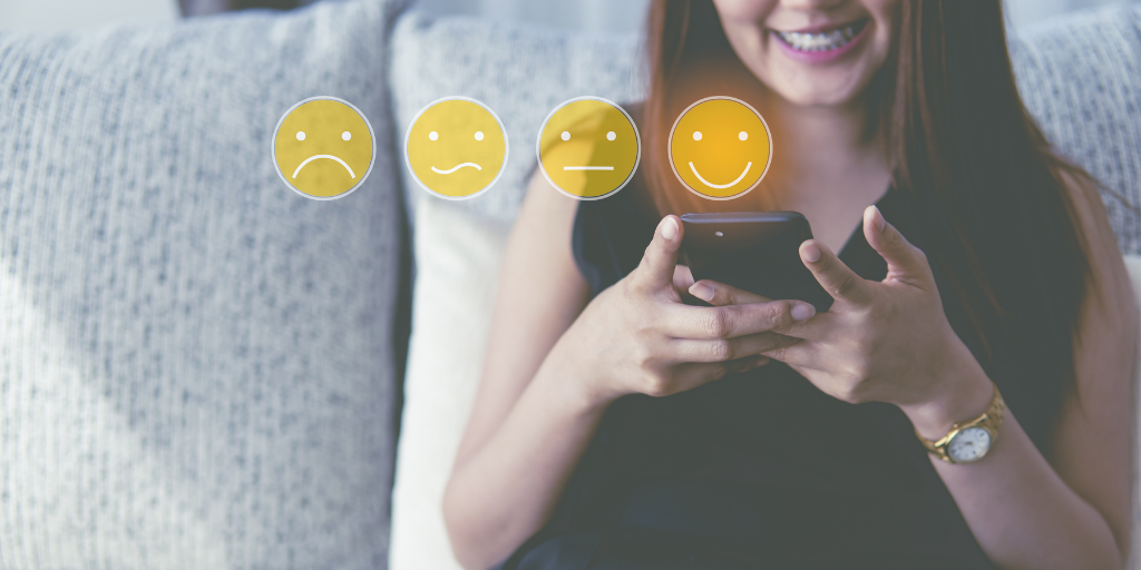 Woman sitting on couch holding smartphone with smile face icon for rating from feedback.