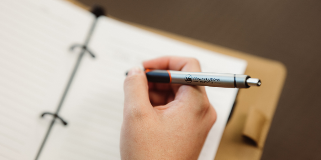 Hand poised over notebook holding a pen featuring Viral Solutions' name, logo, and phone number.