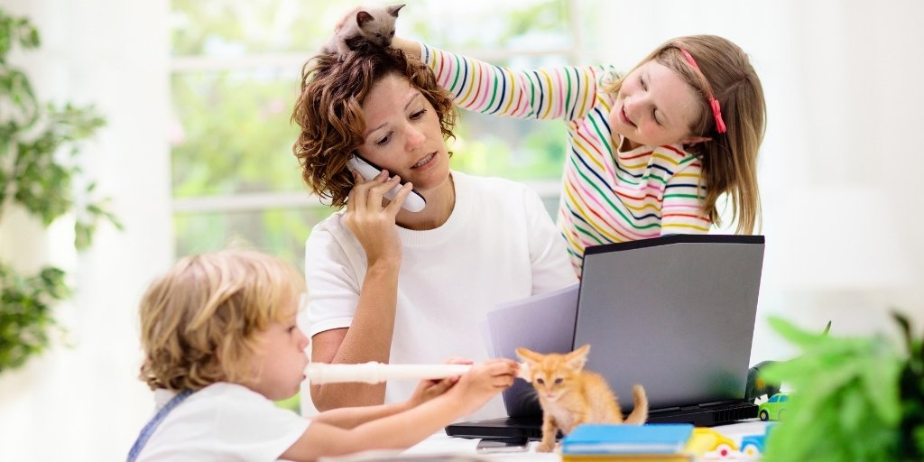 Mother on phone in front of laptop while children pull her hair and play music.