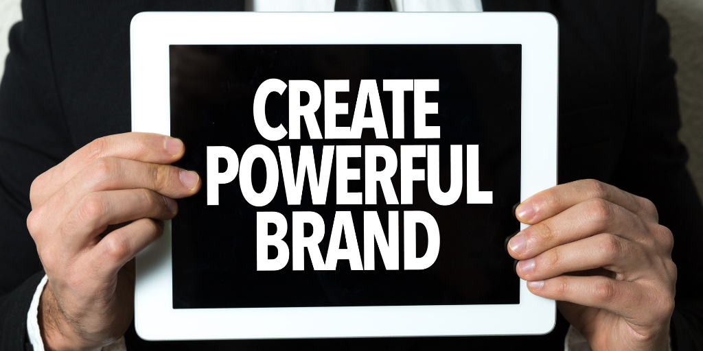 Man in suit holding sign that says 'Create Powerful Brand' highlighting the importance of brand salience.