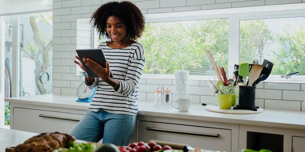 Woman researching recipes on digital tablet while leaning against the counter in her kitchen.