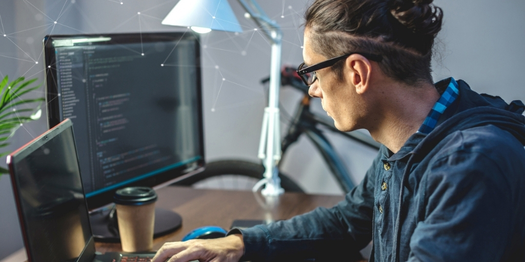 Male IT specialist working in an office and using computers for site migration process.
