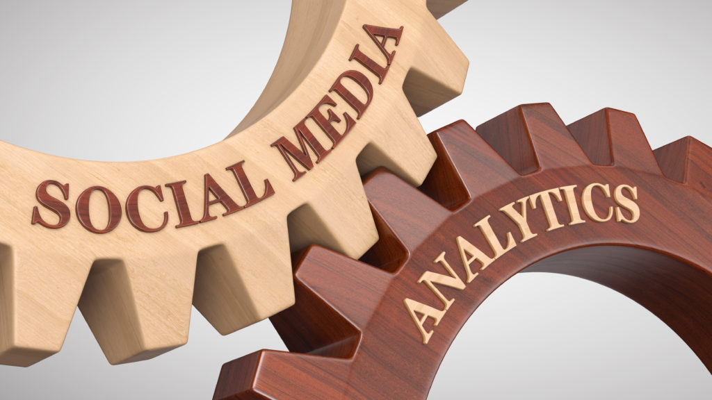 Social media analytics concept showing two gears representing social media and analytics meshing together.