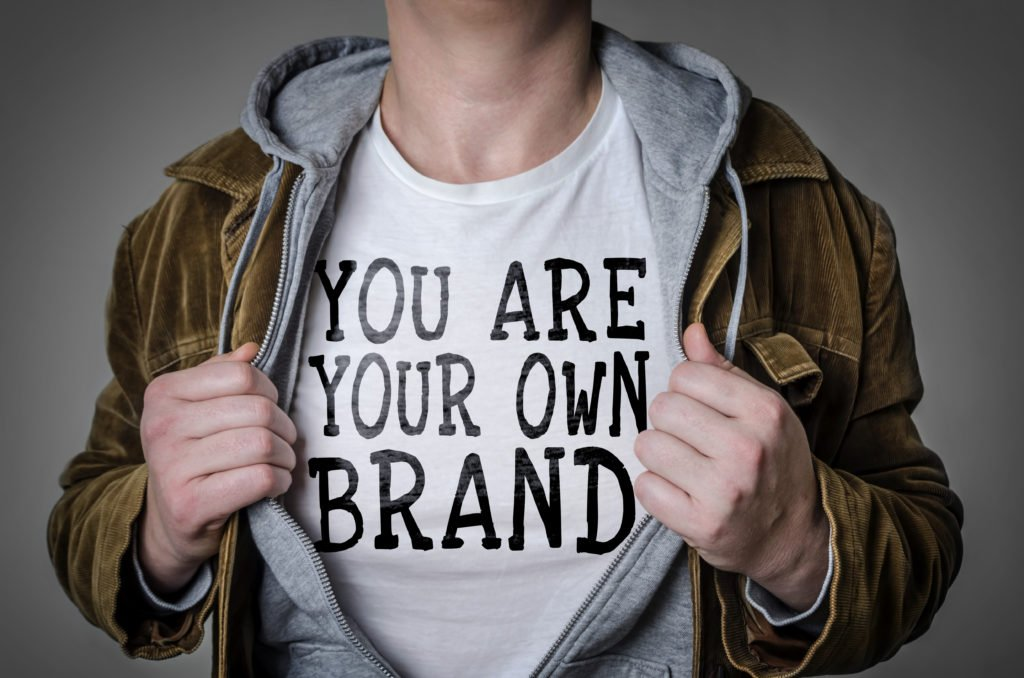 Man with coat open showing t-shirt that says you are your own brand as concept of personal brand vs. company brand.